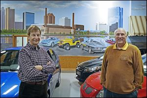 Artist Michael Goettner, left, and David Lawrenz, Nice Car Company owner, show off the mural Mr. Goettner painted at the Ottawa Lake dealership. The 60-foot-by-20 foot work shows local landmarks.
