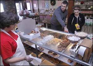 Barb Johnson fills a doughnut order for customers Nick Wiczynski and Sarah Stephens at Wixey Bakery.