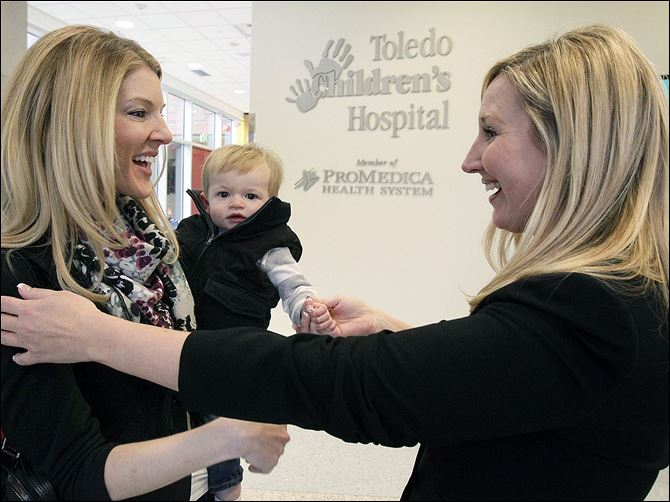 CTY pierce20p kari Kari Stausbaugh holds her son Pierce as they are greeted by Christi Rotterdam, executive director of Toledo Children's Hospital Foundation.