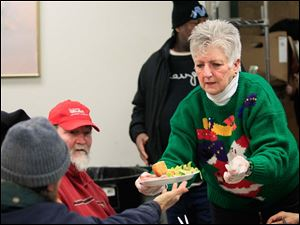 Ann Hodge, a board member at St. Paul's Community Center, hands a meal to an appreciative diner.