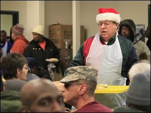 Chuck Hodge delivers a tray of dinners to hungry diners at St. Paul's Community Center on Christmas Eve.