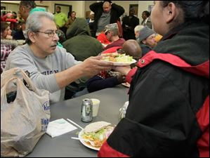 Another diner passes a meal to Gaspar Rodriguez, left, of Toledo, at St. Paul's Community Center.