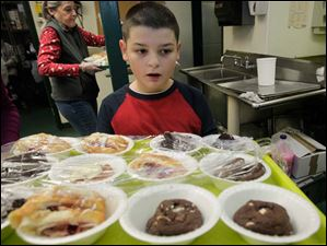 Tommy Bernal, 8, marvels at the dessert options for diners at St. Paul's Community Center's Christmas Eve dinner.
