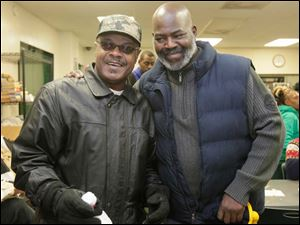 Barry Tipton, left, spends some time with Toledo Mayor Mike Bell on Christmas Eve at St. Paul's Community Center.