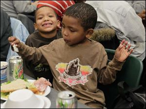 Davontae Finn, 6, and his brother Shawn Finn, 5, of Toledo, take in a meal provided by the community center.