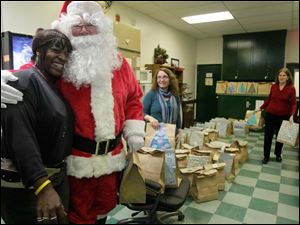 Mimi McNair, left, of Toledo, Santa Claus, Danielle Elchidiac, of Tripoli, Lebanon, center, and Regina Silletti, of Toledo, right hand out gift bags to each diner. The bags contain socks, scarves, mittens, and toiletries, including shampoo, skin cream, and soap.