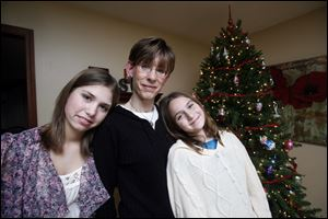Sonja Delaney, center, and her daughters, Olivia Hann, left, 14, and Amelia Hann, 10, pose for a portrait next to their Christmas tree in Waterville.  Through Project Bethlehem they have been able to purchase Christmas gifts for two needy families.