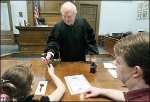 Judge Jack Puffenberger gives a newly adopted girl a gavel with a pick bow while her father, Tim Krego, right, watches in Lucas County Probate Court.