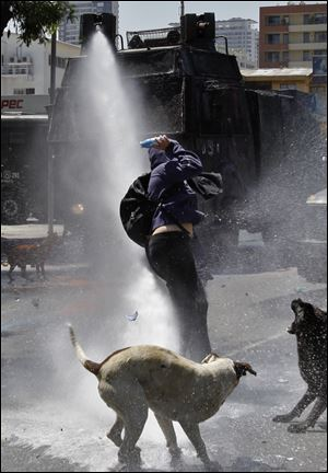 Dogs bark as a hooded youth gets into position to throw a bottle filled with paint as he is sprayed by a police water cannon in Santiago, Chile, in October.