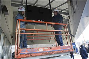 Brint Electric employees Ben Kolar, left, and Brent Feldman install a new electronic sign at the TARTA Park Station at Madison Avenue and Erie Street in downtown Toledo. The sign is part of a new system to provide riders with up-to-the-second information about bus locations and time of arrival.
