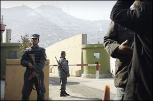 Afghan policemen stand guard outside of Kabul police headquarters, where an American adviser was killed, today.