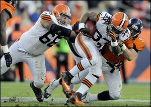 Browns running back Trent Richardson is tackled by Denver's Keith Brooking in the fourth quarter. Richardson later injured his ankle while pass-blocking for Colt McCoy.