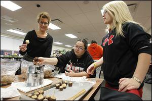 Kim Murry, left, co-coordinator of the high school program, and high school students Sarah Keith, center, and Valerie Nofziger make buckeyes for a caroling event and party.