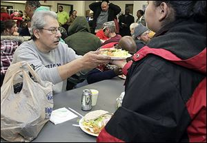 Another diner passes a meal to Gaspar Rodriguez, left, of Toledo at St. Paul's Community Center during its Christmas dinner for residents and guests Monday.