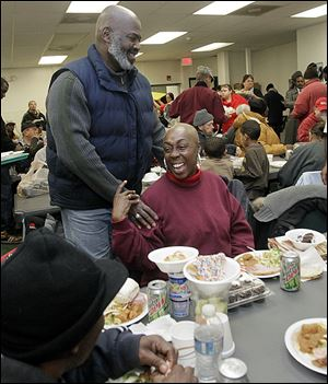 Mayor Mike Bell talks to Mischell Montgomery of Toledo at St. Paul's Community Center during its Christmas dinner for residents and guests.
