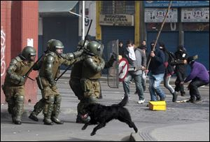 A dog runs as police clash with student protesters in Santiago, Chile, in July.