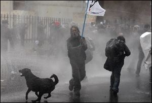 A dog runs in the spray as riot police use water cannons against demonstrators during a protest against the premiere of a documentary about the late Gen. Augusto Pinochet in Santiago, Chile in June.