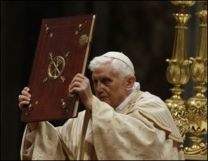 Pope Benedict XVI holds up the book of the gospel as he celebrates the Christmas Eve Mass today in St. Peter's Basilica at the Vatican.