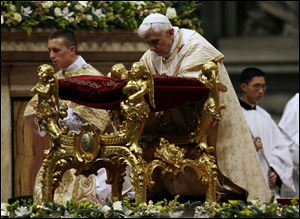 Pope Benedict XVI kneels today as he celebrates the Christmas Eve Mass in St. Peter's Basilica at the Vatican.