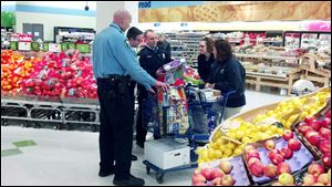 Police officers load a cart at Meijer on East Alexis Road to replace gifts for Nicole Kosci­uczyk's four children that were stolen in a burglary Monday.