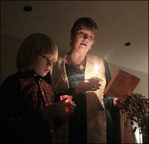 The Rev. Lynn Kerr, right, and her son, Rowan, 11, left, sing Silent Night.'