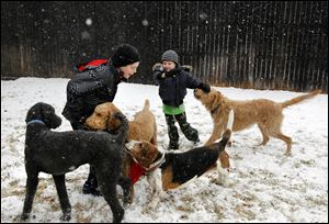 Walker Bowerman, 10, left, and Hughes Bowerman, 6, plays with family dogs in the snow today in Arlington, Texas.