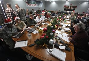 Volunteers take phone calls from children asking where Santa is and when he will deliver presents to their house, during the annual NORAD Tracks Santa Operation, at the North American Aerospace Defense Command, or NORAD, at Peterson Air Force Base, in Colorado Springs, Colo.