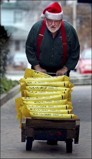 Roger McCreight, a hardware store employee, brings up the remaining bags of rock salt from the basement inventory to stock in the store for customers Monday in Maplewood, Mo., in anticipation of wintry weather.