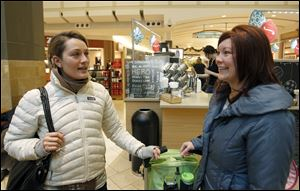 Former Toledoan Mandi Dillin of Los Angeles, left, and Sara Matuszewski of Toledo speak about shopping as they wait for coffee at Westfield Franklin Park mall Wednesday.
