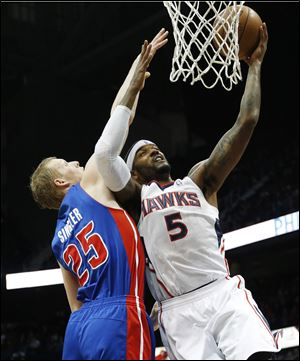 Atlanta Hawks small forward Josh Smith goes up for a basket as Detroit Pistons small forward Kyle Singler defends tonight in Atlanta.