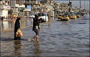 An Iraqi family make their way through flood water, after heavy rain fell in Baghdad, Iraq.