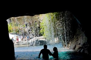 The Hyatt Regency Maui Resort & Spa pool offers an unusual swimming experience with waterfalls spilling over a cave leading to a children's water play area in Lahaina, Hawaii.