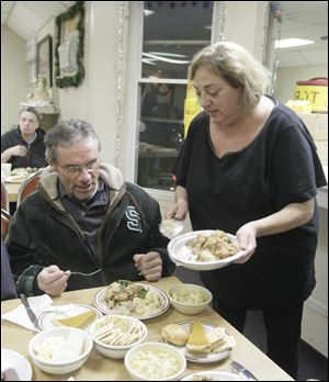 Tom Ward, of Toledo, is served stuffing by Connie Case, of Sylvania Township. The Toledo Gospel Rescue Mission hosts 60 people for Christmas dinner at the facility in Toledo, Ohio on December 25.
