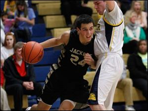 Whitmer High School player Luke Hickey defends as Perrysburg High School player Nick Moschetti  drives the baseline.