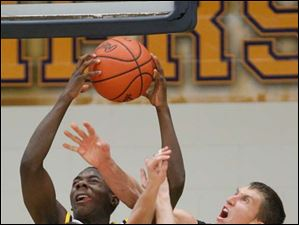 Whitmer High School player Jon Ashe, 22, battles for a rebound with Perrysburg High School players Tyler Freeman, 22, and Bryant Byrd, 11.