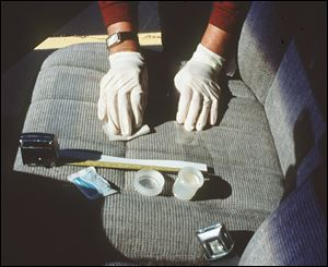 A researcher checks the seat of a car belonging to a worker at an Alabama machine shop. A study concluded that workers at the shop were contaminating their cars with beryllium dust.