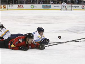 Toledo Walleye player Joey Martin, 14, and Cincinnati Cyclones player David MacDonald, 12, dive for the puck.