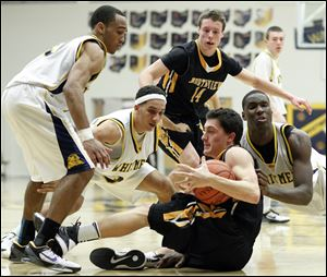 Whitmer's Ricardo Smith (10) Marcus Elliott (32) and  Nigel Hayes (23) battle Sylvania Northview's Chris Nowicki (44), on floor,  for a loose ball. In the background is Northview's Connor Hartnett (14).