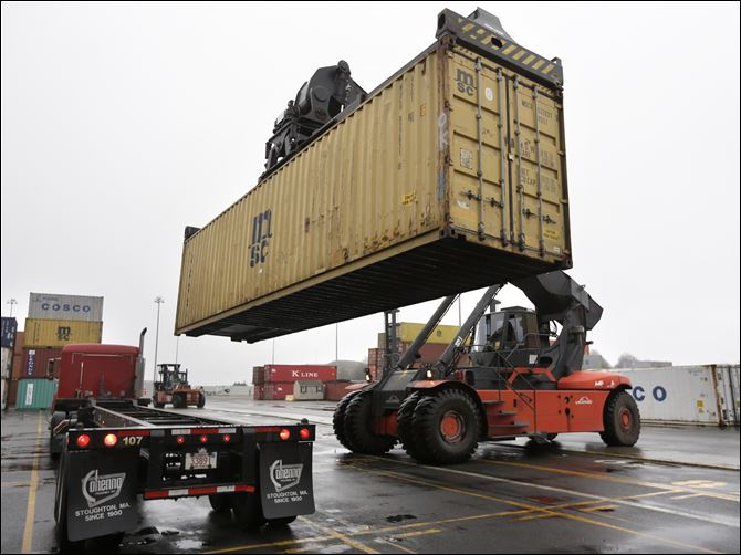 A reach stacker operated by a longshoreman A reach stacker operated by a longshoreman, right, places a shipping container on a tractor trailer truck at the Port of Boston, in Boston. The longshoremen's union may strike if they are unable to reac