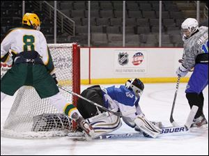 Anthony Wayne High School goalie Alec Smith, 1, covers the puck as teammate Harrison Pawliski, 16, helps defend the shot attempt of Oregon Clay High School player R.J. Stringham, 8, during the first period at the Huntington Center.