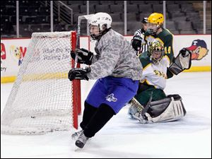 Anthony Wayne High School player Mike McDougall, 17, gets the puck past Oregon Clay High School goalie Matt Hennessy, 30, during the second period.