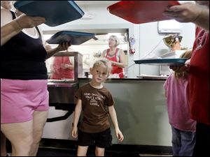 Kimberly Slover, 5, is framed by trays of food carried by Debra Born, left, and Roger Steinman, right, at the Helping Hands of St. Louis Outreach Center in East Toledo, Tuesday, June 19, 2012.  The facility, which has a food pantry, soup kitchen, and clothing center, is celebrating its 30th anniversary.  Steinman is Kimberly's grandfather, Born is his fiance.
