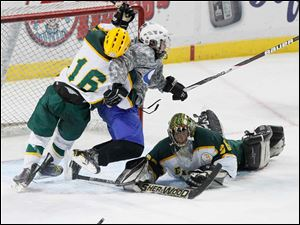 Oregon Clay High School player Jake Richard, 16, hits Anthony Wayne High School player Mike McDougall, 17, as Clay goalie Matt Hennessy, 30, makes the save during the third period.