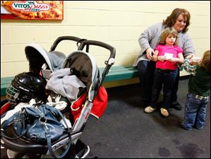 Kris Walborn, of Swanton, center, treats her daughter, Gabby, 5, and son Troy, 2, to hot chocolate after Troy's first skating experience. Walborn said her son wasn't totally sold on ice skating.