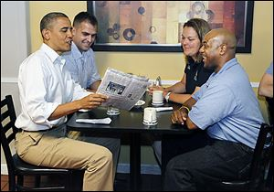 President Obama holds The Blade while sitting in Rick's City Diner in Toledo with Daniel Schlieman, back left, heather Finfrock, and James Fayson.