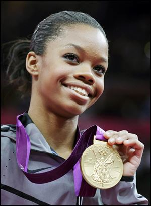 Gabrielle Douglas of the United States displays her gold medal in the artistic gymnastics women's individual all-around competition at the 2012 London Olympics.