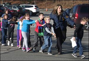 Connecticut State Police lead a line of children from Sandy Hook Elementary School in Newtown, Conn., after a shooting at the school claimed the lives of 20 first graders and six staff members.
