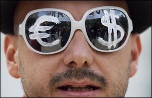 A protester wears glasses with the euro and dollar symbols painted on the lenses before protesting the conservative government's handling of the economic crisis and to demand fresh elections, in Madrid.