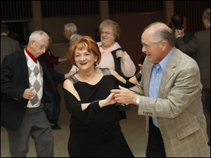 Janet Frederick of West Toledo, center left, shared a dance with Harold Hutchinson, of Toledo, right, Friday evening during this year's Paramount's Jingle Bell Ball.
