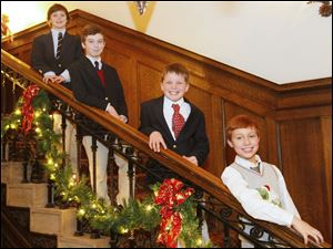 From left, Spencer Atkins, 11, Roman Marra, 10, Thomas Barrow, 10 and Rocco Marra, 9, pose for a photograph down the staircase at the Christmas Tea Dance at the Toledo Club.